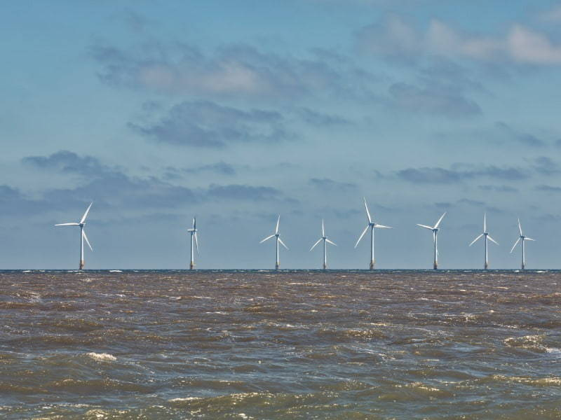 view of offshore wind farm at sea